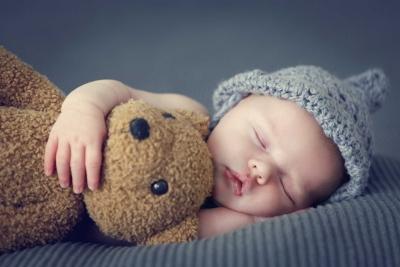 Ein Baby mit grauer Mütze schläft mit einem Teddybär im Arm